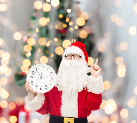 man in costume of santa claus with clock showing twelve pointing finger up over tree lights background