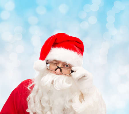 close up of santa claus in glasses winking over blue lights background photo