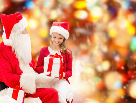 nicolas: smiling little girl with santa claus and gifts over red lights background Stock Photo