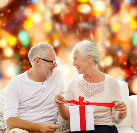 couple couch: happy senior couple with gift box over red lights background Stock Photo