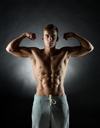 スポーツ、ボディービル、強さ、人のコンセプト - 若い男が黒の背景で上腕二頭筋を表示 写真素材