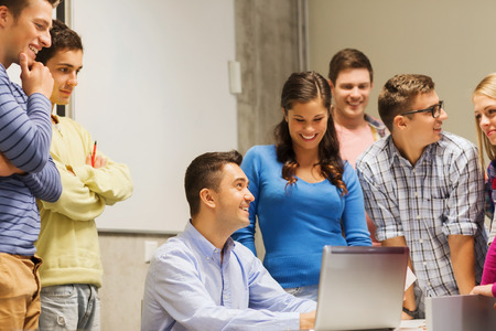 group of smiling students and teacher with papers, laptop computer in classroom photo