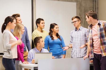 groep lachende studenten en leraar met laptop computer in de klas Stockfoto