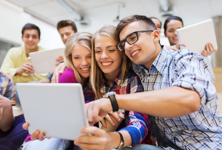 taking video: group of smiling students with tablet pc computers taking photo or video indoors