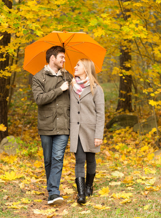 walking in the rain: smiling couple with umbrella walking in autumn park