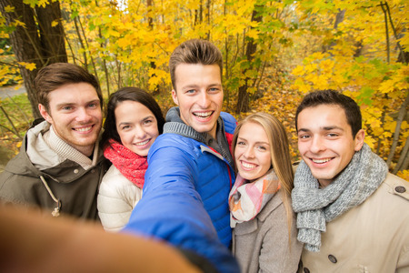group of smiling men and women taking selfie with smartphone or camera in autumn park photo