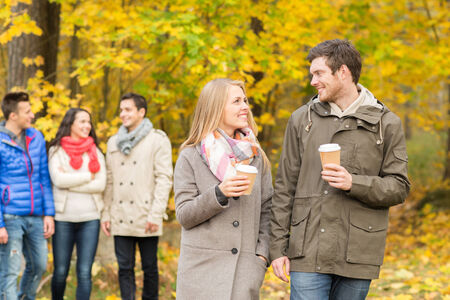 coffee cups: group of smiling men and women walking with paper coffee cups in autumn park