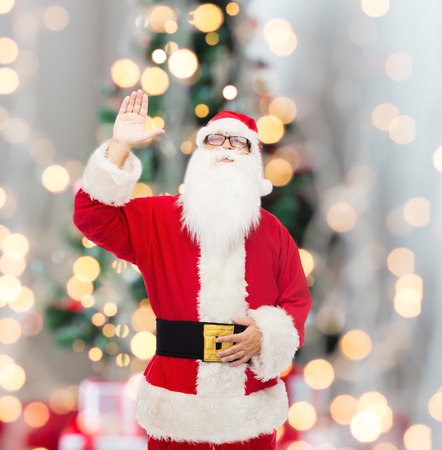 man in costume of santa claus waving hand over tree lights background photo