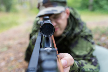 sniper rifle: close up of young soldier, ranger or hunter with gun in forest