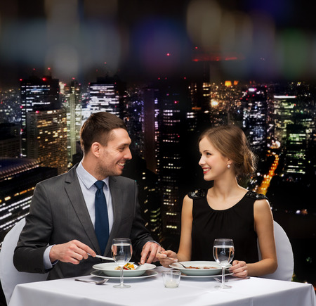 restaurant, couple and holiday concept - smiling couple eating main course at restaurant photo