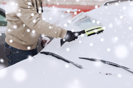closeup of man cleaning snow from car windshield with brush photo