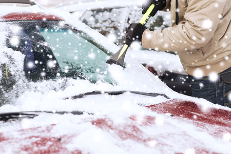 car body: transportation, winter, weather, people and vehicle concept - closeup of man cleaning snow from car windshield with brush