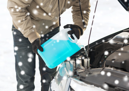 winter season: closeup of man pouring antifreeze into car Stock Photo
