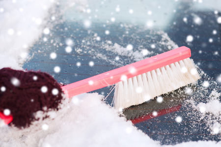 transportation, winter, weather, people and vehicle concept - closeup of woman cleaning snow from car windshield with brush photo