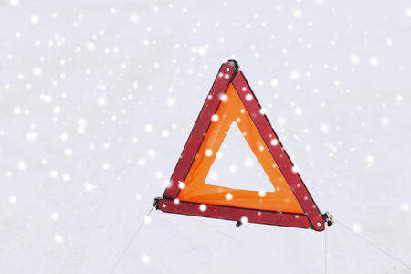 notable: transportation and winter concept - closeup of warning triangle on snow