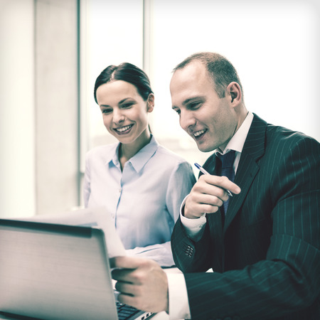 businessman and businesswoman with laptop computer and papers having discussion in office photo