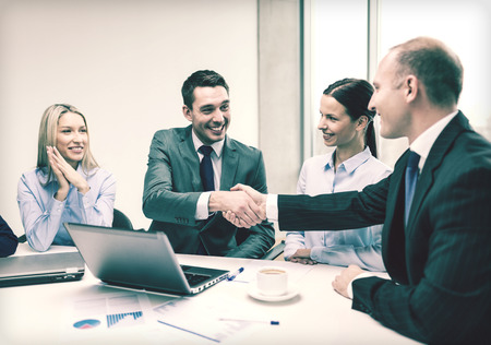 businessman smiling:  two smiling businessman shaking hands in office