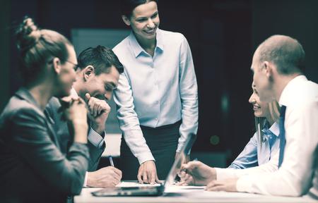 empresarial: negocios, tecnología y concepto de oficina - sonriendo jefa hablar con equipo de negocios Foto de archivo