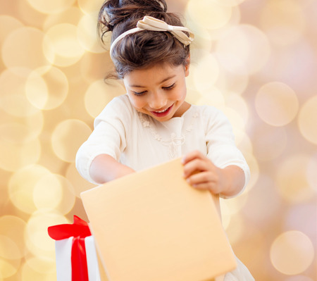 grateful:  smiling little girl with gift box over beige lights background