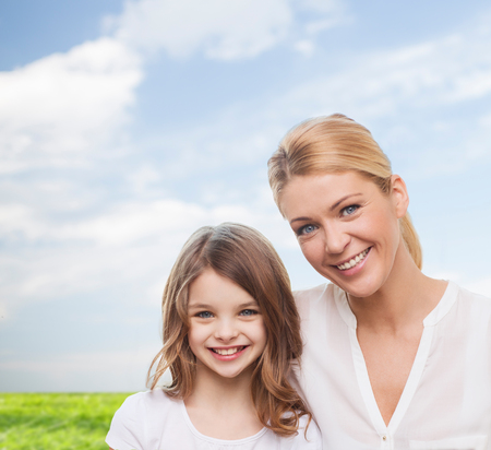 pretty girl: smiling mother and little girl over blue sky and grass background
