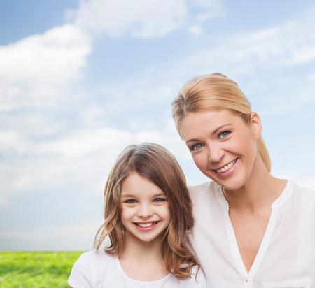 jeune fille adolescente: souriante m�re et petite fille sur le ciel bleu et l'herbe fond