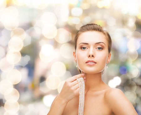 bride bangle: beautiful woman with pearl earrings and necklace over lights background