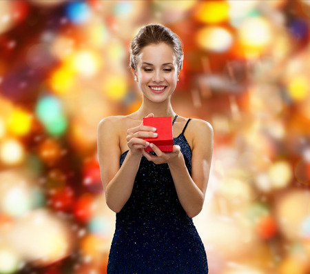 proposal of marriage: smiling woman in dress holding red gift box over red lights background