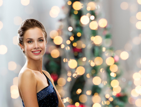 evening:  smiling woman in evening dress over christmas tree lights background Stock Photo
