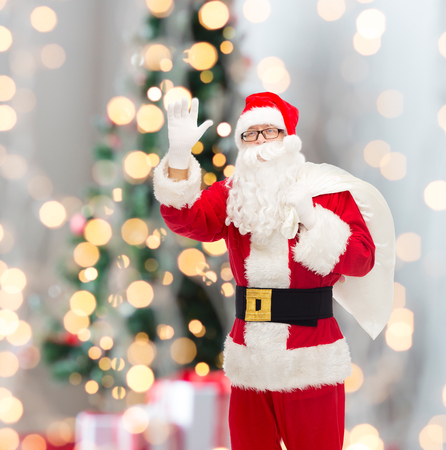 christmas, holidays, gesture and people concept - man in costume of santa claus with bag waving hand over tree lights background photo