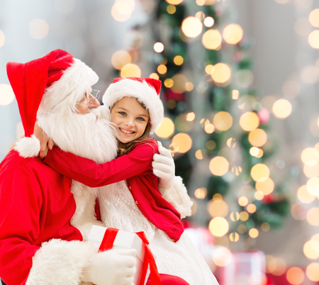 holidays, celebration, childhood and people concept - smiling little girl hugging with santa claus over christmas tree lights background Archivio Fotografico