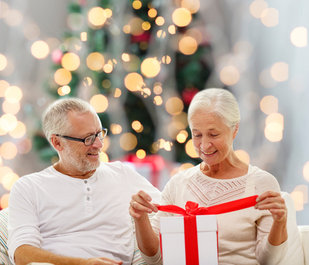 family, holidays, age and people concept - happy senior couple with gift box over christmas tree lights background photo
