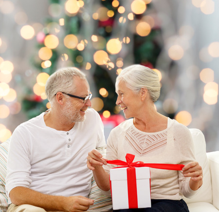 happy senior couple with gift box over christmas tree lights background