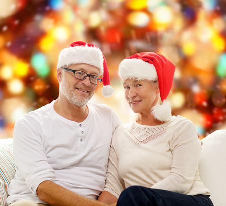 family, holidays, christmas, age and people concept - happy senior couple in santa helper hats sitting on sofa over red lights background photo