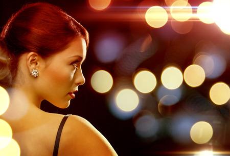 beautiful woman in evening dress wearing diamond earrings 스톡 콘텐츠