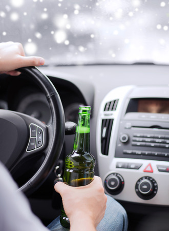 drinking driving: close up of man drinking alcohol while driving car Stock Photo