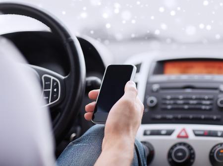 close up van de man met behulp van smartphone tijdens het rijden de auto