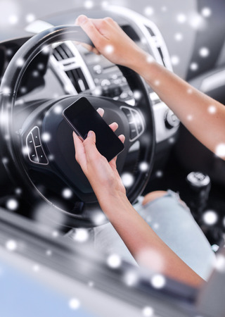close up of woman using smartphone while driving car photo