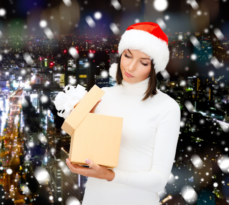 woman in santa helper hat with gift box over snowy night city background photo