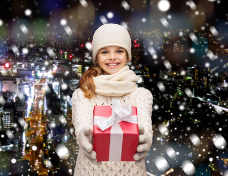 christmas, holidays, childhood, presents and people concept - dreaming girl in winter clothes with gift box over snowy city background photo