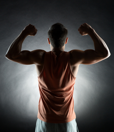 man arm: sport, bodybuilding, strength and people concept - young man showing biceps over black background from back