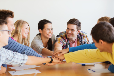 education, teamwork and people concept - smiling students with papers putting hands on top of each other Stock Photo - 32783094