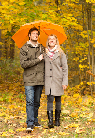 couple in rain: love, relationship, season, family and people concept - smiling couple with umbrella walking in autumn park