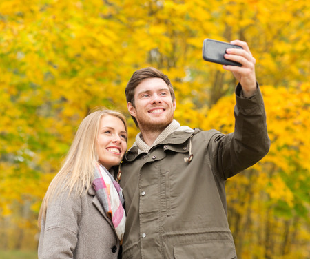 internet love: love, relationship, family and people concept - smiling couple hugging and taking selfie in autumn park