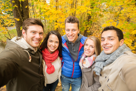 technology, season, friendship and people concept - group of smiling men and women taking selfie with smartphone or camera in autumn park photo