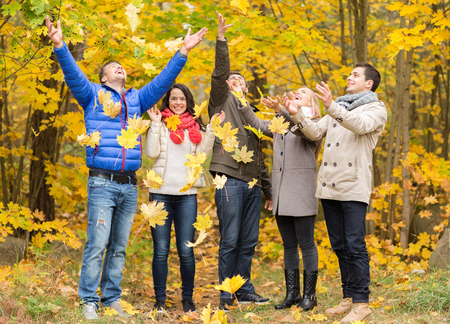 love, relationship, season, friendship and people concept - group of smiling men and women having fun in autumn park photo