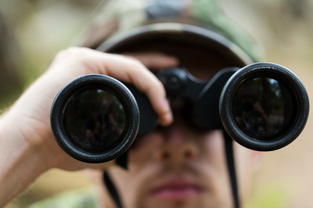 body guard: hunting, war, army and people concept - close up of young soldier, ranger or hunter with binocular observing forest Stock Photo