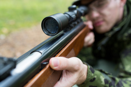 sniper rifle: hunting, war, army and people concept - close up of young soldier, ranger or hunter with gun in forest Stock Photo