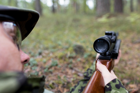 hunting, war, army and people concept - close up of young soldier, ranger or hunter with gun in forest photo