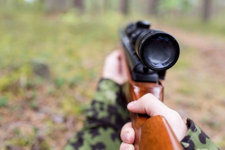 infantryman: hunting, war, army and people concept - close up of young soldier, ranger or hunter with gun in forest Stock Photo