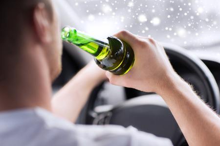 el transporte, el alcohol, el vehículo y las personas concepto - cerca del hombre de beber alcohol mientras se conduce un coche Foto de archivo